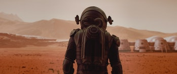 Back view of astronaut wearing space suit walking on a surface of a red planet. Martian base and rov...