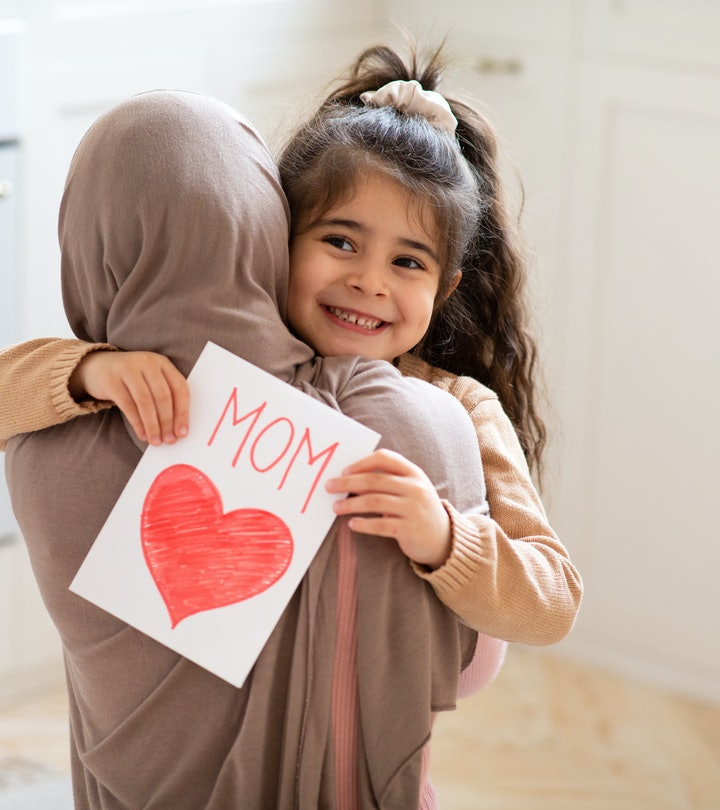 Smiling little girl holding greeting card for Happy Mother's Day with drawn red heart and hugging her muslim mom. Loving islamic family bonding together at home, closeup shot with free space