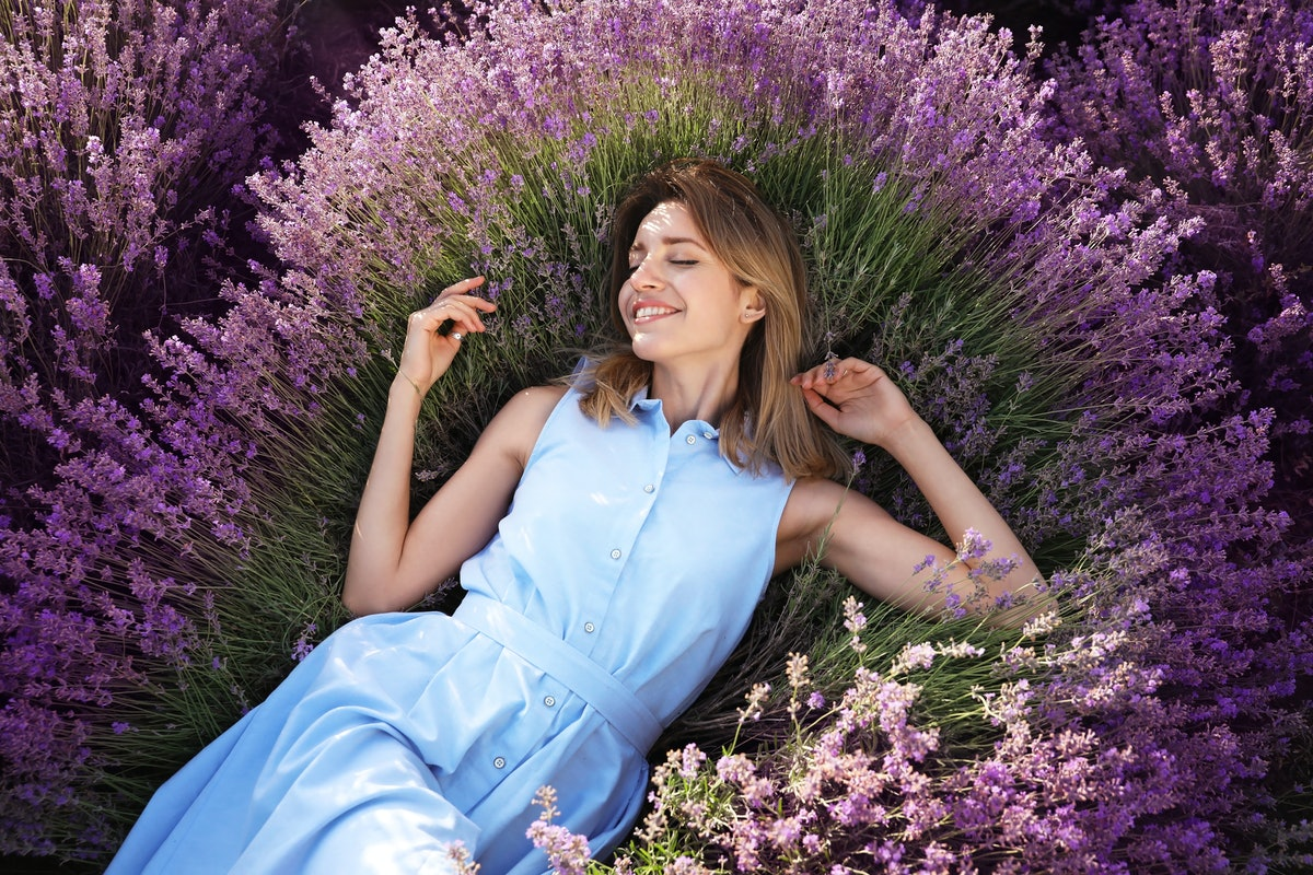 Young woman lying in lavender field on summer day