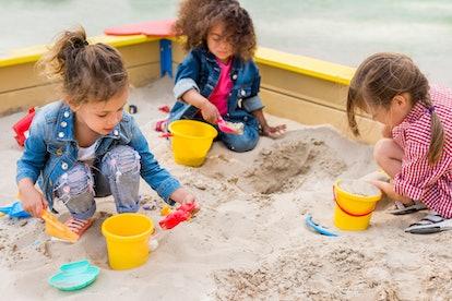three girls playing in a sandbox