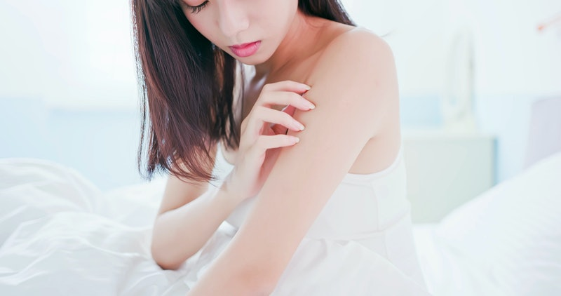 woman feel bad and scratching her arm because of dry skin at home