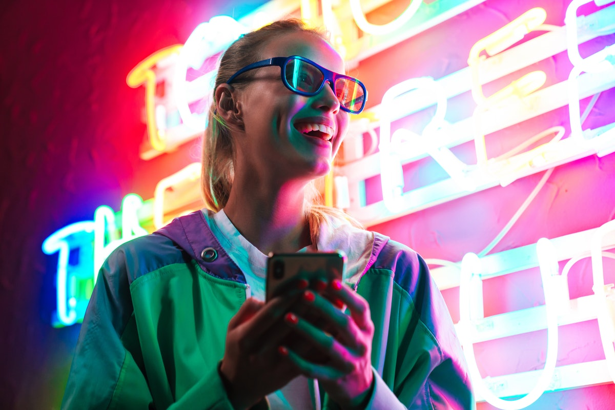 Image of beautiful young caucasian woman in 3D glasses holding smartphone over multicolored neon text sign