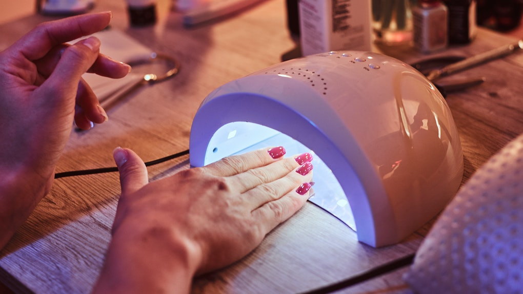 Client with red varnish at manicure salon cairfully waiting when her nails become dry  in UV light. Closeup shoot.