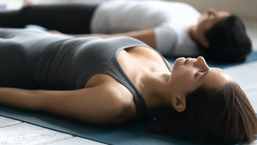 During yoga therapy session women lying in Shavasana Corpse Dead Body asana close up focus on Caucasian young girl with closed eyes. Pose releases fatigue, helps to relax muscles, no stress concept