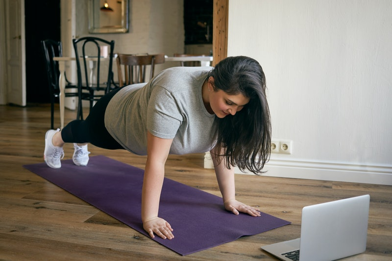 Energetic self determined overweight young woman in sneakers standing in plank with feet and hands on mat, reteating exercises after professional fitness instructor, watching tutorial online on laptop