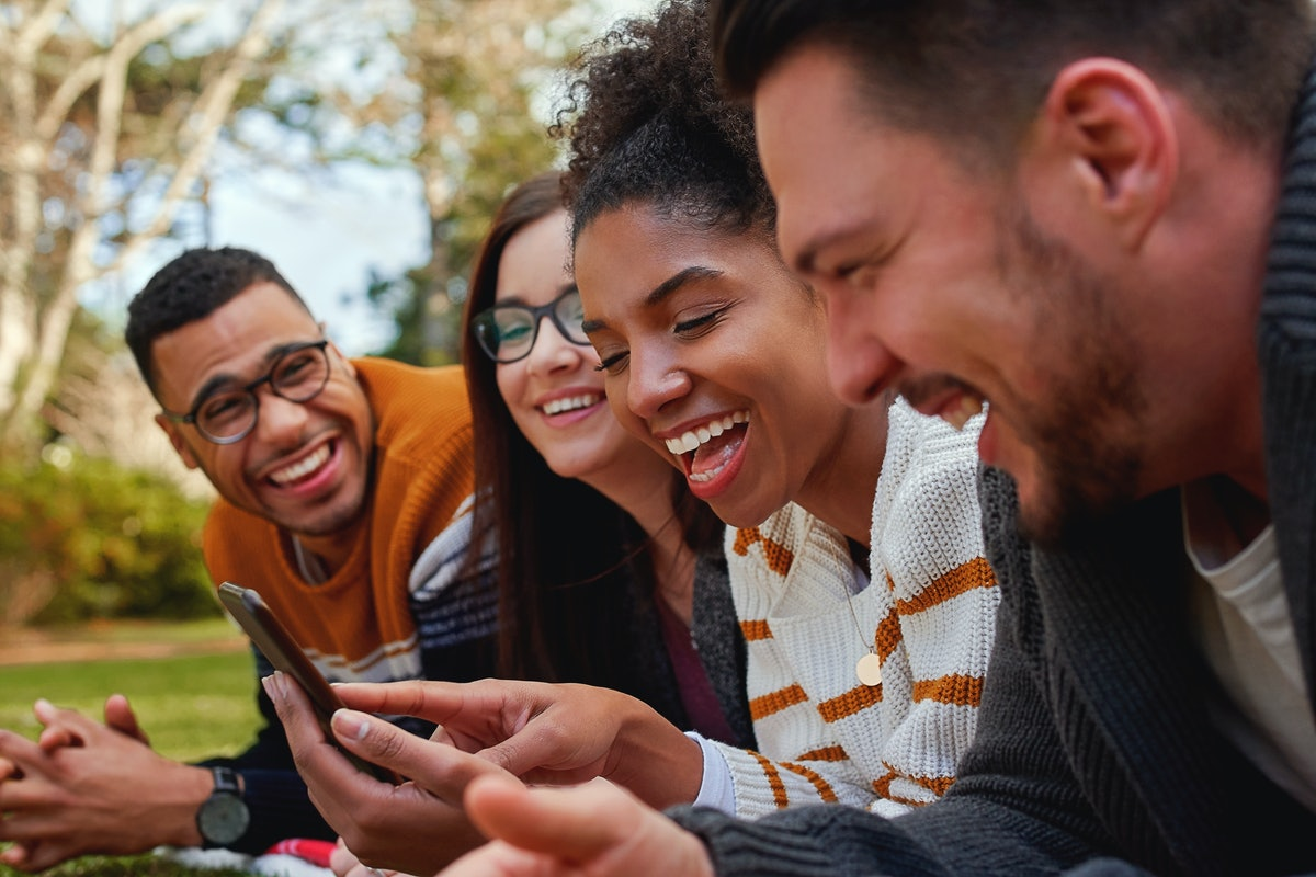 A group of friends laugh while looking at their phone.