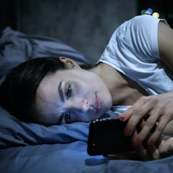 Smartphone addiction. Young tired female looking at her mobile phone screen, lying in bed late at ni...
