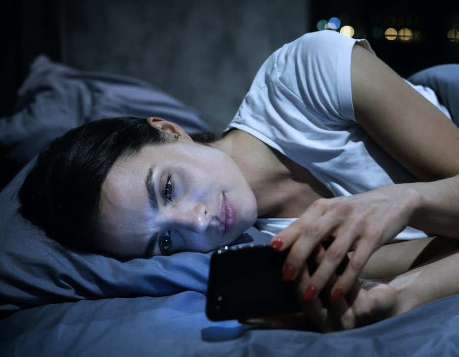 Smartphone addiction. Young tired female looking at her mobile phone screen, lying in bed late at night, scrolling her social media news feed