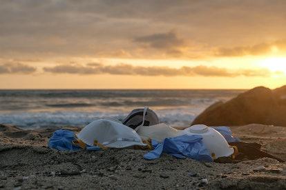 Medical waste,mask and plastic gloves garbage trash on sunset sea shore,coronavirus covid pollution ...