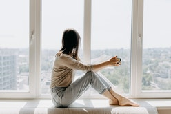 Young woman looking through the window with a city view, sitting on a windowsill, drinking coffee or...