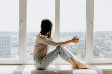 Young woman looking through the window with a city view, sitting on a windowsill, drinking coffee or tea in the morning.
