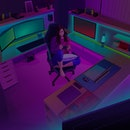 Staying at home during the pandemic playing video games. A girl sits on a gaming chair at a desk playing a computer or console game in a purple and green lit room.