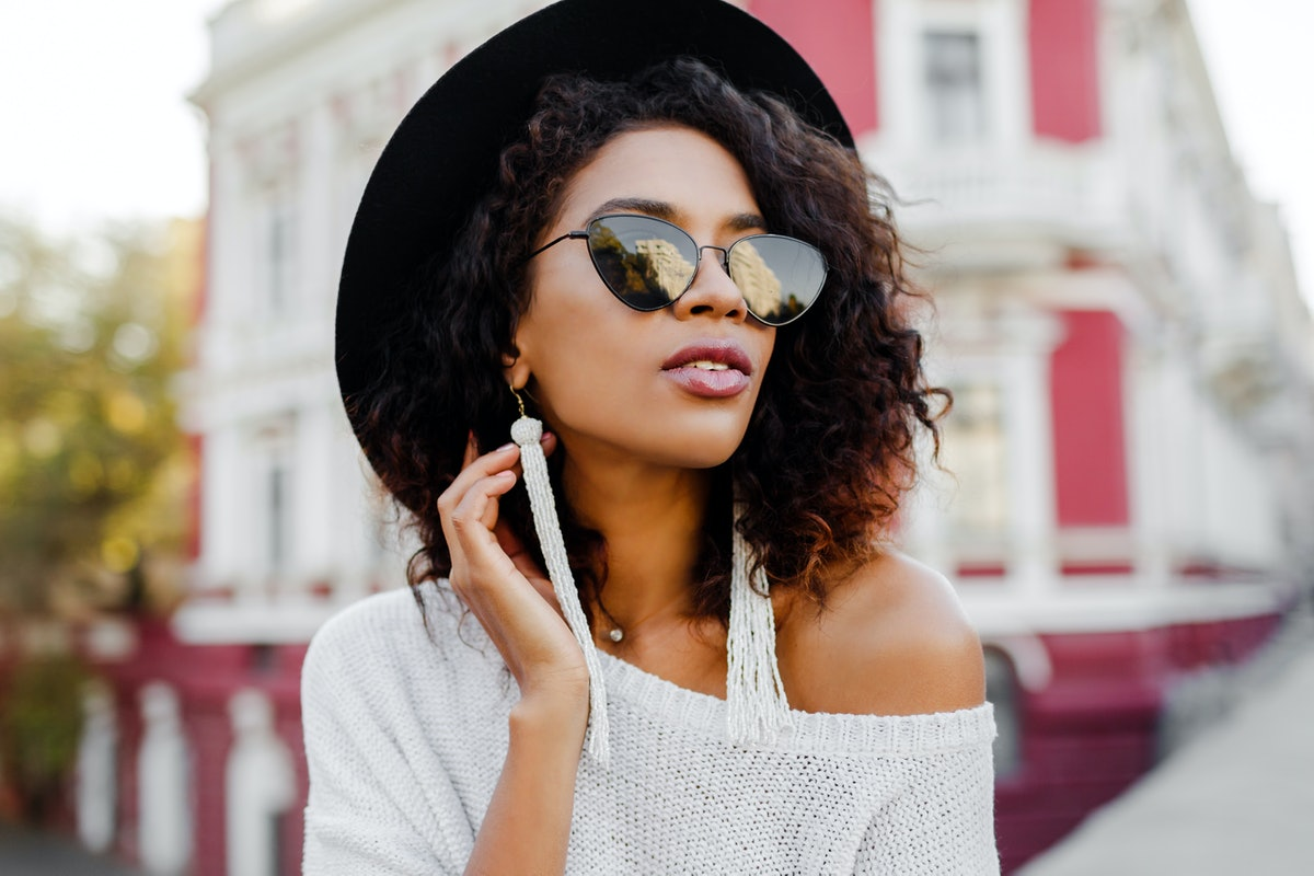 Close up portrait of fashionable black woman with stylish Afro hairs posing outdoor. Urban backgroun...