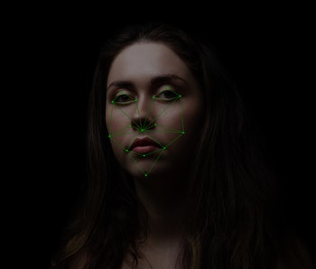 A young woman looks at the screen with a map of light green dots on her face. It is cast by a machine for facial recognition.