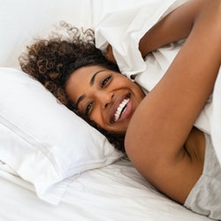 Cheerful young woman lying on bed playing with blanket and looking at camera. African girl feeling fresh after nap on bed with copy space. Laughing woman having fun while embracing pillow and blanket.