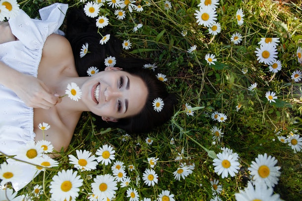 Beautiful woman on a flower garden enjoying her time outdoors. pretty girl relaxing outdoor, having fun, holding plant, happy young lady and spring green nature, harmony concept