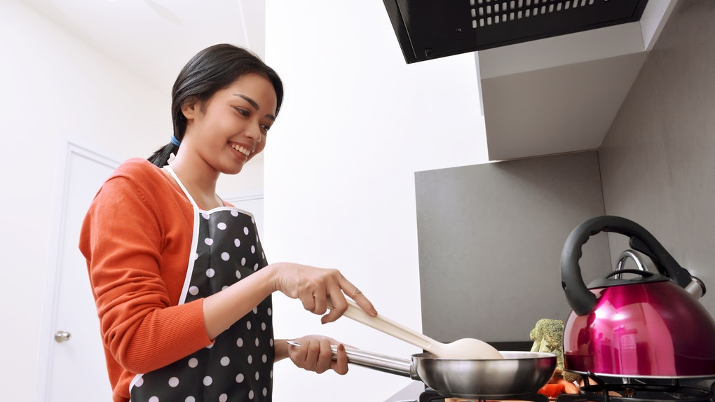 A happy woman cooks something over her stove at home.