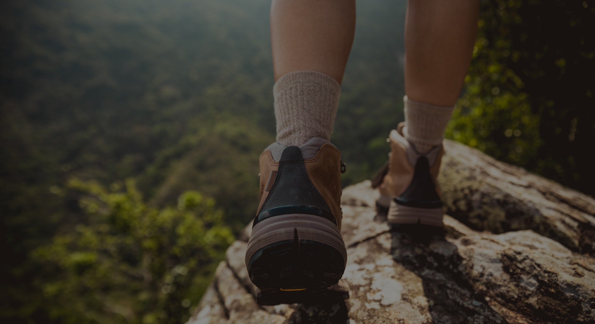 Successful hiker enjoy the view on mountain top cliff edge