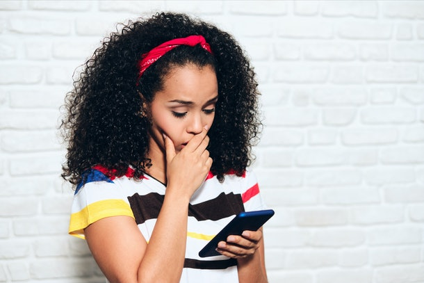Sad african american woman reading bad news on cell phone. Black girl showing sadness and desperation for message on mobile telephone. Hispanic person with smartphone
