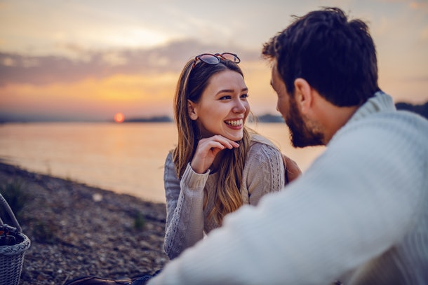 Cute smiling Caucasian brunette sitting on coast near river with her loving boyfriend and flirting. In background is sunset.