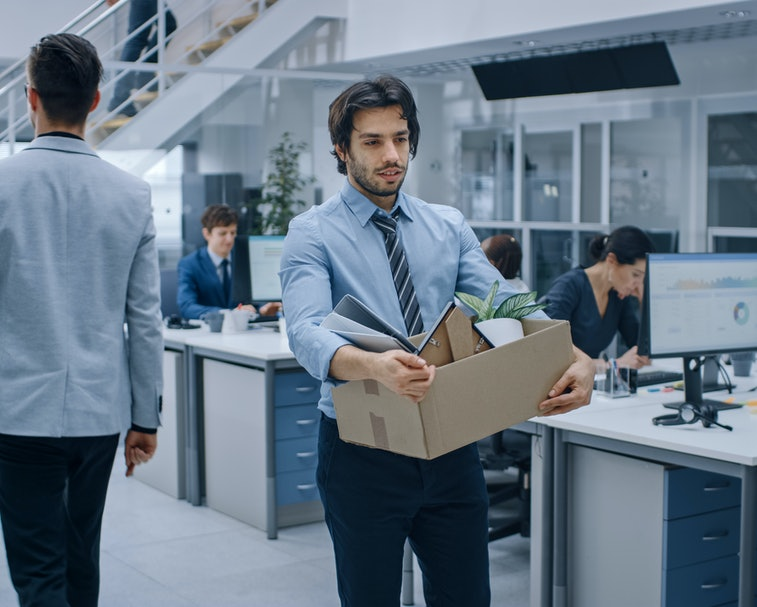 Sad Fired / Let Go Office Worker Packs His Belongings into Cardboard Box and Leaves Office. Workforc...