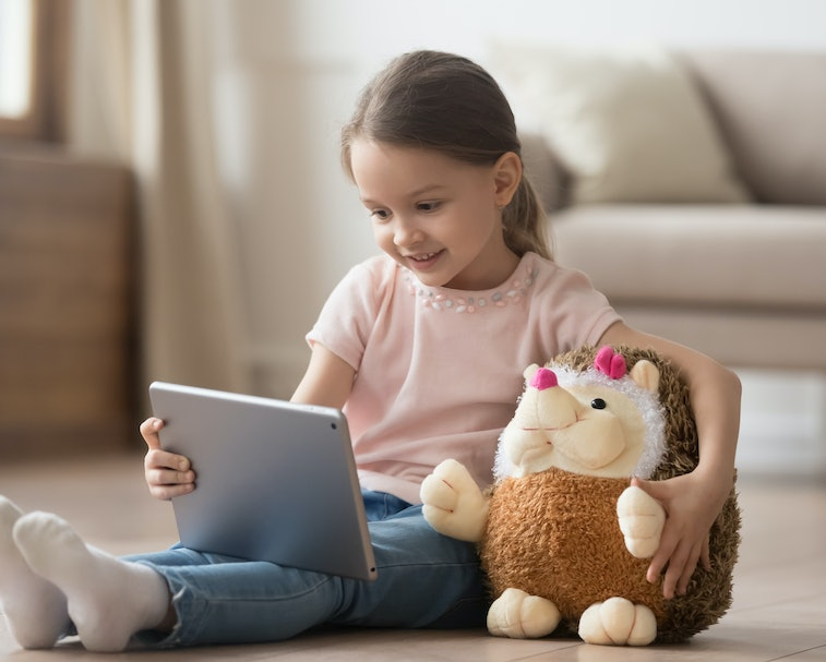 Curious little child girl having fun using digital tablet alone embracing toy sitting on floor, happ...