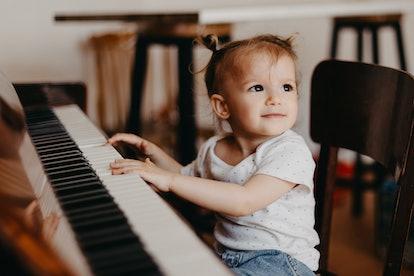 toddler sitting at piano