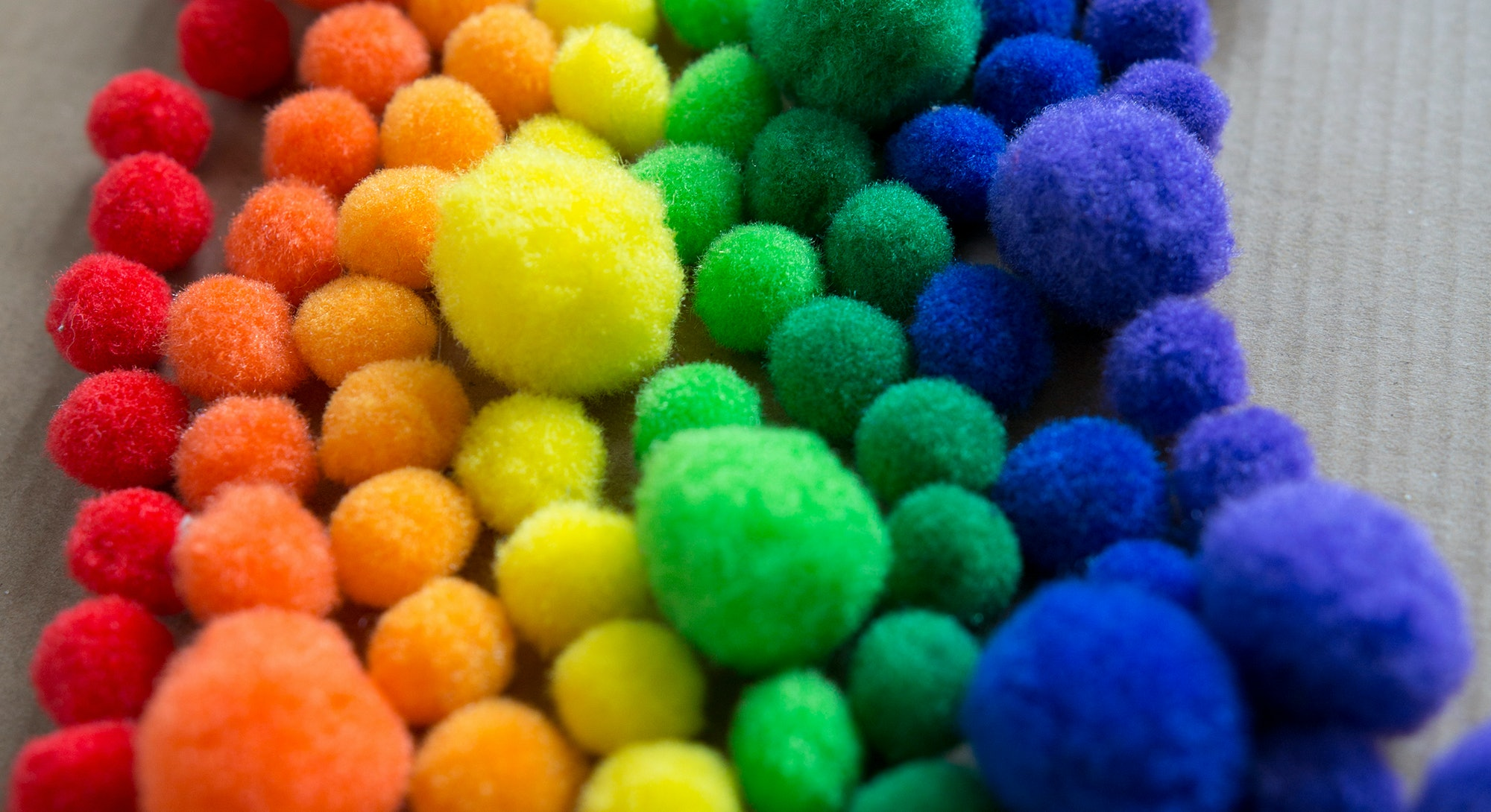 Happy, colorful rainbow pattern made of fluffy pom pom balls.