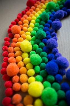 Happy, colorful rainbow pattern made of fluffy pom pom balls.