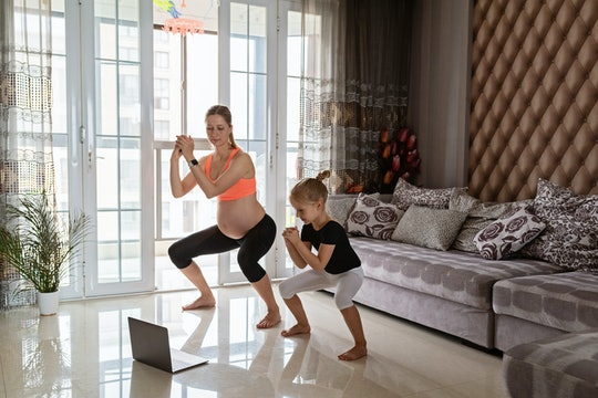 Pregnant woman and kid in sport clothing exercising at home. Online training during coronavirus covi...