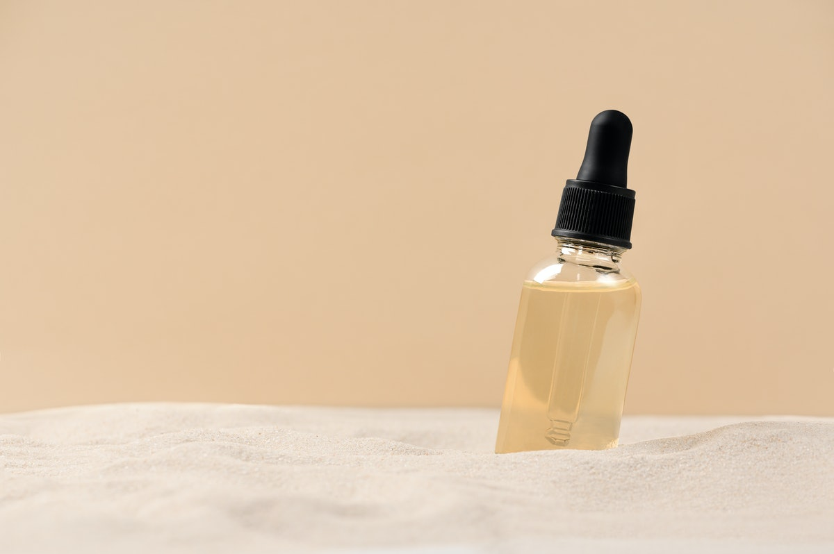 Skincare with beauty cosmetic face serum. Glass bottle with a pipette on a natural background with s...