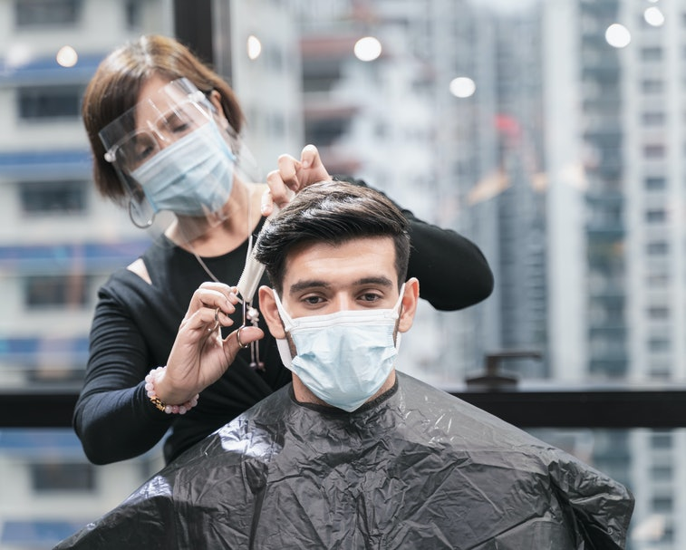 Hairdresser with security measures for Covid-19 or coronavirus, hair cut a man in a medicine mask, social distance, cutting hair with a medical mask, eye mask in a beauty salon, new normal 2020