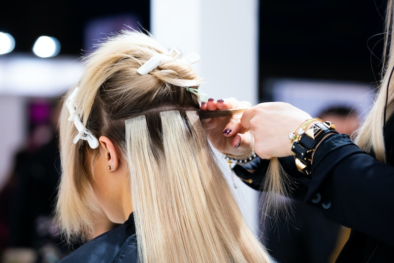 Professional hairdresser making hair extensions for blonde girl in a beauty salon
