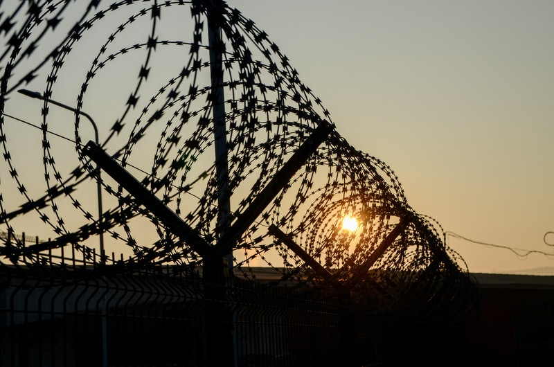 Close-up of sharp razor wire fence at sunset. Barbed tape. Rusty metal barbered wire on jail. Concept of prison, immigration, detention, boundary or war. Prison barber wire near jail or camp.