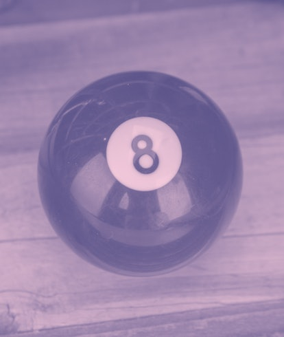 A magic eight ball sits on a distressed wood texture with lots of room for text! Vintage magic 8 ball!