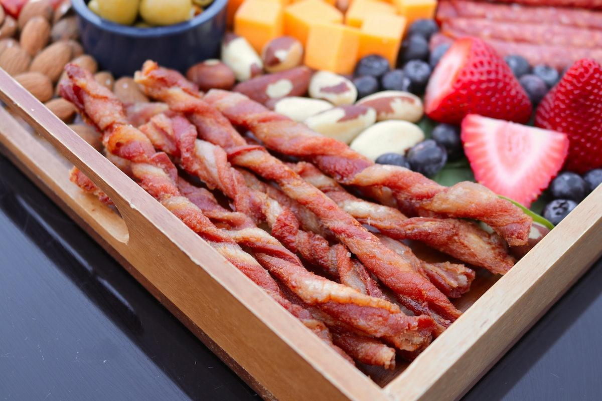 Bacon twists sit on a charcuterie board.