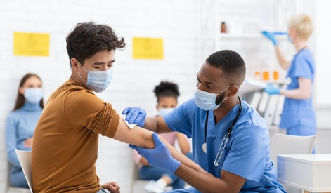 Covid-19 Vaccination. Asian Male Patient Getting Vaccinated Against Coronavirus Receiving Covid Vaccine Intramuscular Injection During Doctor's Appointment In Hospital. Corona Virus Immunization