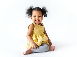 Happy little girl in a yellow dress sitting