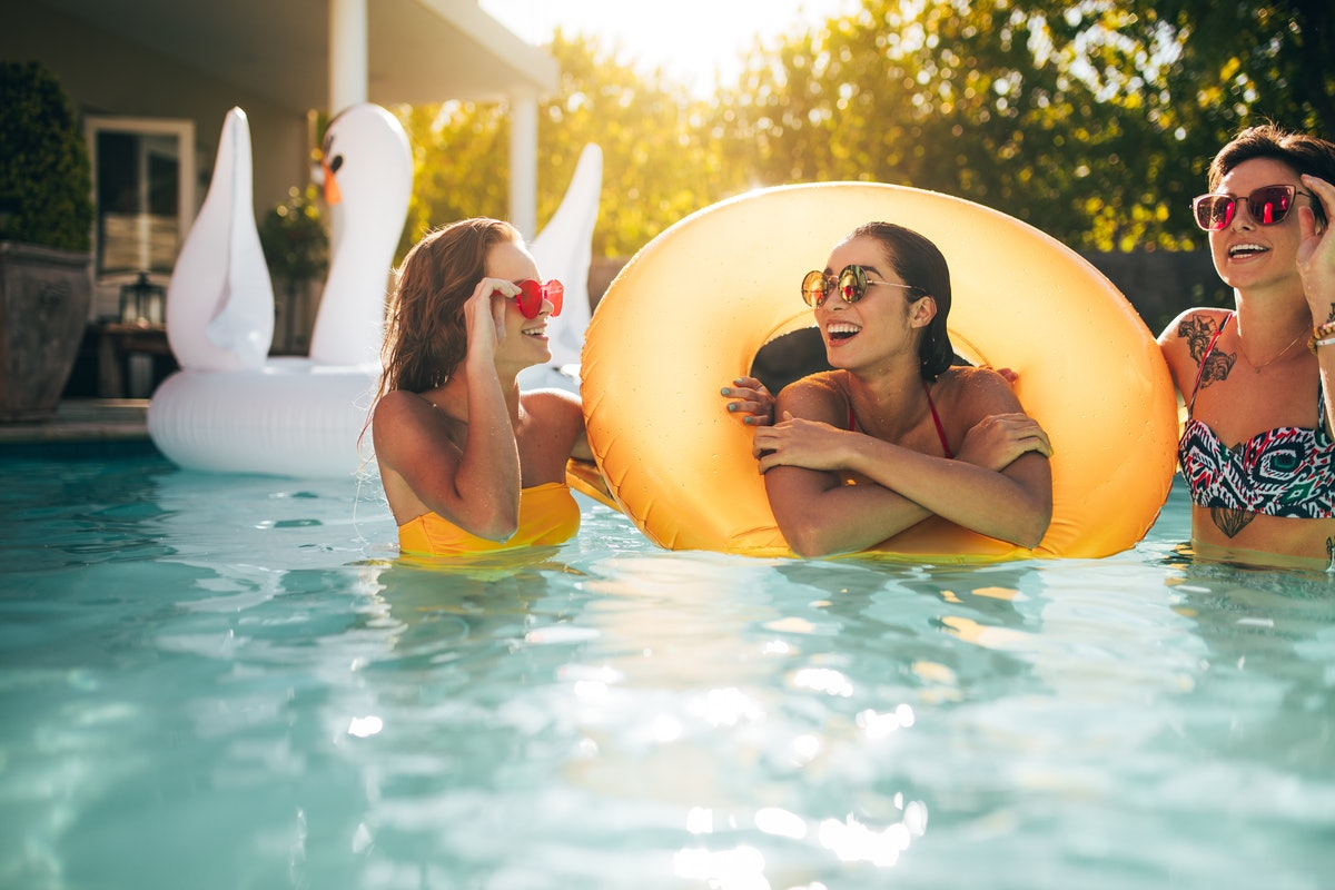 Happy young female friends in swimming pool with inflatable ring. Smiling women enjoying in a pool.