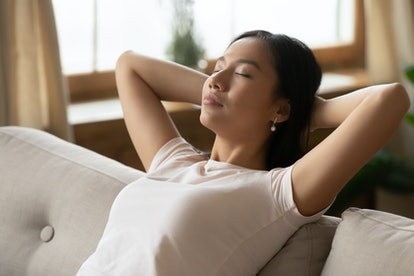 Close up image asian ethnicity millennial woman resting leaned on couch in living room. Breath fresh air, reduce fatigue, enjoy weekend free time at modern home alone, no stress inner harmony concept