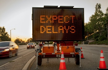 """Mobile Electronic Traffic Sign stating """"expect Delays"""" taken at sunset with traffic blurred driving ..."""