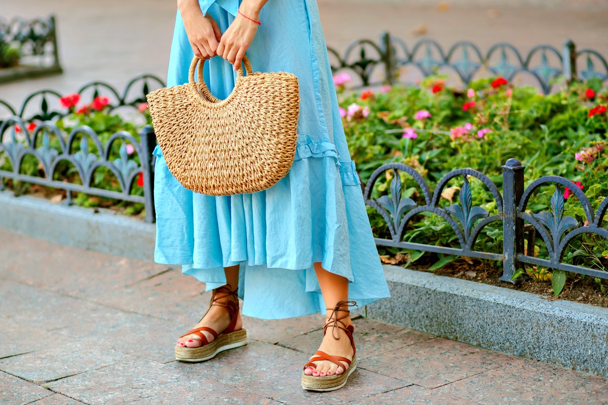 Close up fashion street details of tender stylish woman posing at Europe city, wearing blue maxi dress, straw hat and gladiator sandals, summertime.