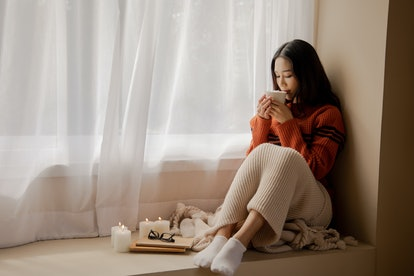 Young beautiful Asian woman holding cup of coffee and marshmallows on top, sitting at home and looking out the window. Happy girl drinking chocolate in sweater in cold weather winter