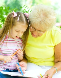 little girl with her grandmother drawing