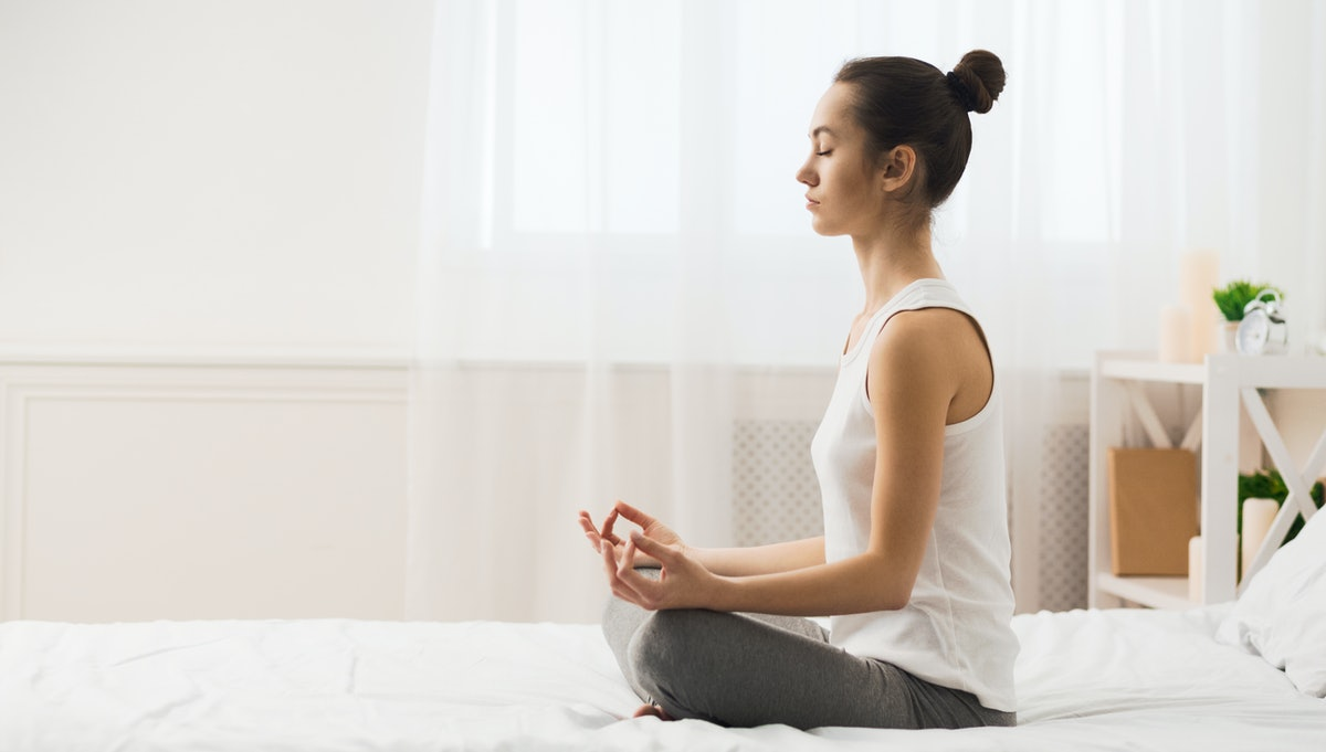 Morning Meditation. Woman Practicing Yoga On Bed After Waking Up, Side View, Free Space