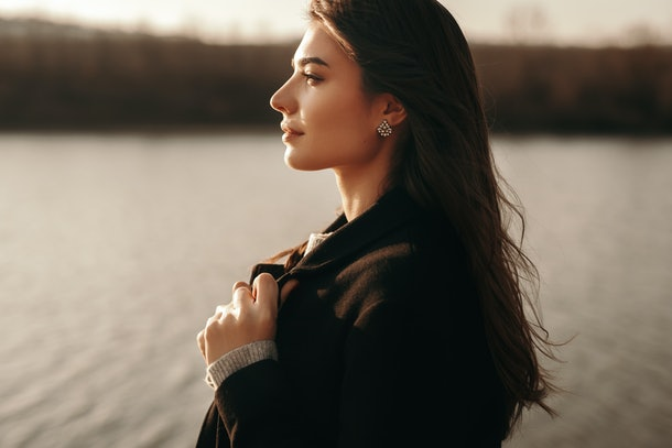 Side view of confident young female with long dark hair wearing stylish warm coat standing on lake shore and looking away thoughtfully