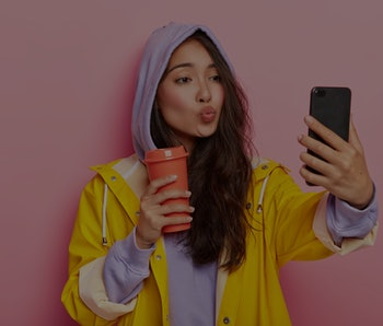 Lovely teenage girl with Asian appearance, keeps lips folded, sends kiss at camera of cellphone, tak...