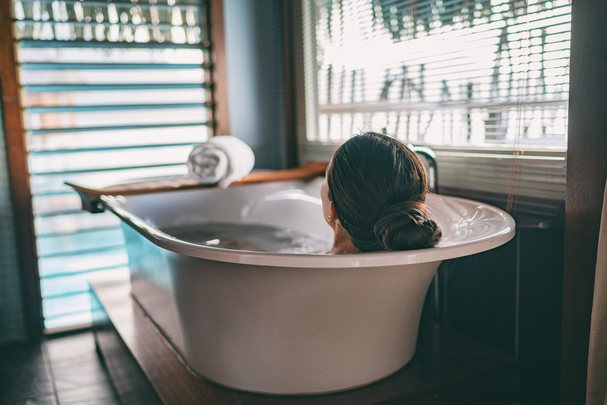 Bath taking woman relaxing in bathtub of hotel room at luxury overwater bungalow resort in Bora Bora...