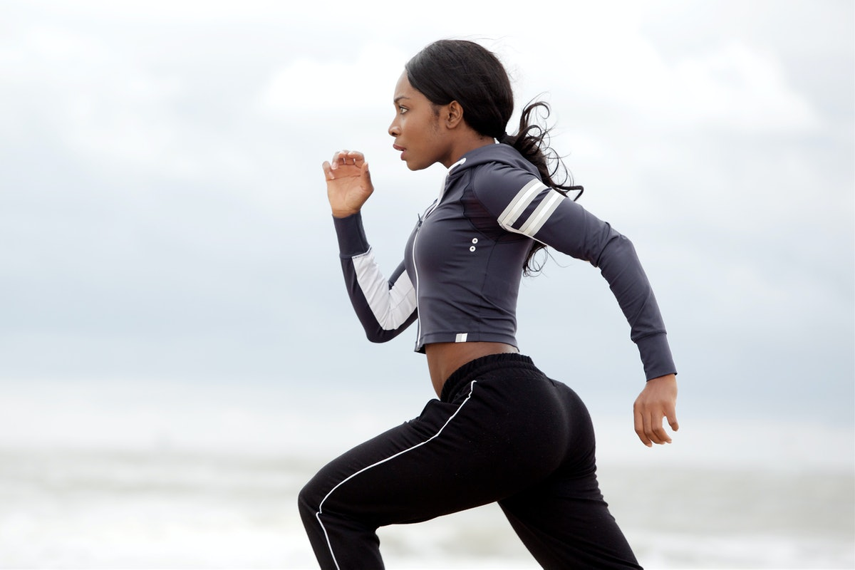 Side portrait of sporty young black woman running