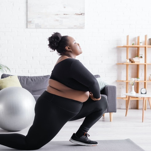 A woman lunges on a yoga mat to stretch her butt after sitting all day.